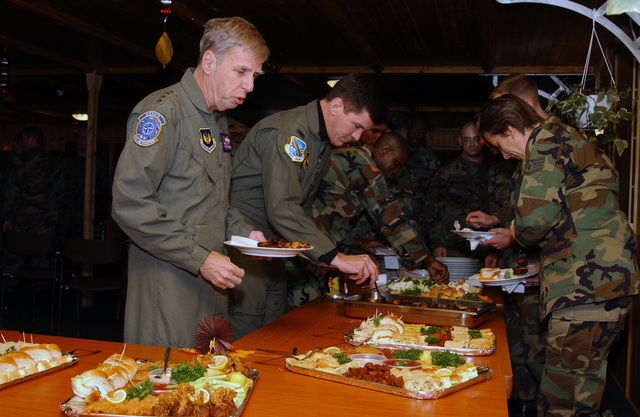 U.S. Air Force GEN. Robert H. Foglesong (left), Commander of U.S. Air Force Europe, shares a Thanksgiving meal with COL. Joe Abbott (second from left), 401st Air Expeditionary Wing Commander, Aviano Air Base (AB), Italy, MASTER SGT. Danny Shoemore (third from left), of the 435th Vehicle Readiness Squadron, Ramstein AB, Germany, STAFF SGT. Suellyn Nuckolls (right), from the 3rd Communications Squadron, Elmendorf Air Force Base, Alaska, and other Airmen deployed in support of Operation Joint Forge at Camp Butmir, Sarajievo, Bosnia, on Nov. 24, 2004. (USAF PHOTO by MASTER SGT. Valerie J. Weaver) (Released)