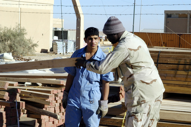 A uniformed Iraqi interpreter (right) assists a young Iraqi student, who is enrolled in the Iraqi Construction Apprentice Program (ICAP), select a piece of 2x4 lumber in order to build a shelf frame. The ICAP is trade school run by the US Navy (USN) Naval Mobile Construction Battalion 23 (NMCB-23), stationed in Al Asad, Iraq, and is designed to train Iraqi civilians in such construction skills as carpentry, masonry, electrical, and plumbing
