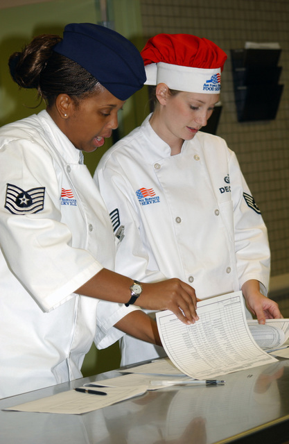 U.S. Air Force TECH. SGT. Octavia Richardson (left), 56th Services Squadron, assistant dining hall and production manager, and STAFF SGT. Melissa Decker, shift leader, discuss food production logs at the Ray V. Hensman Dining Facility, Luke Air Force Base, Ariz., on Dec. 1, 2004.(U.S. Air Force PHOTO by AIRMAN First Class Sarah Elliott)  (Released)