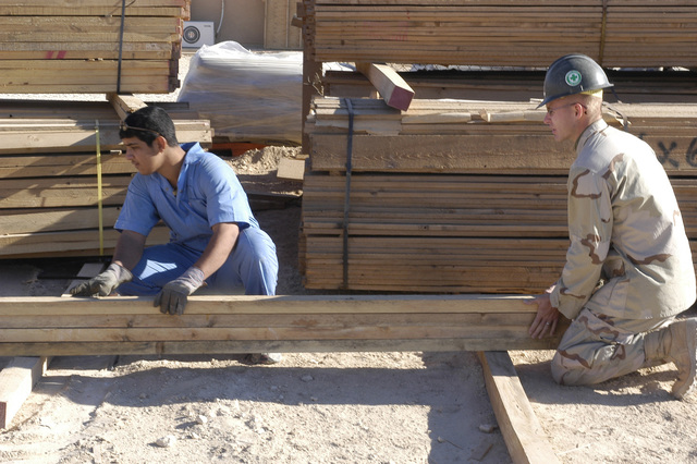 US Navy (USN) Builder Second Class (BU2) Darrell Smith (right), USN Naval Mobile Construction Battalion 23 (NMCB-23), instructs an young Iraqi student, who is enrolled in the Iraqi Construction Apprentice Program (ICAP), about choosing quality lumber in order to build a shelf frame. The ICAP is trade school run by the NMCB-23, stationed in Al Asad, Iraq, and is designed to train Iraqi civilians in such construction skills as carpentry, masonry, electrical, and plumbing