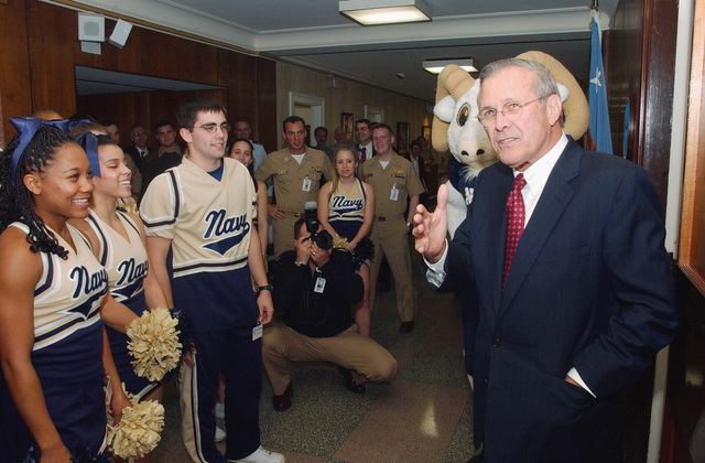 U.S. Secretary of Defense Donald Rumsfeld greets the US Naval Academy (USNA) cheerleaders and mascot, Bill the Goat, outside his office at the Pentagon.  The cheerleaders led a pep-rally through the halls of the Pentagon in anticipation of the upcoming 105th Army-Navy football game on Saturday. (DoD photo by JOC Craig Strawser) (Released)
