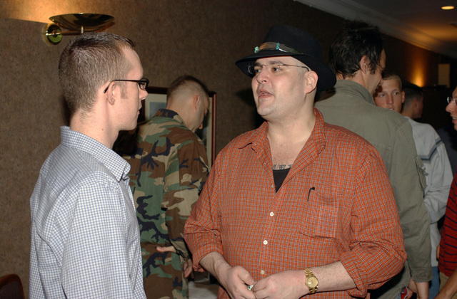 Lead singer of the Blues Traveler band John Popper (right), talks with U.S. Air Force 728 Air Mobility Squadron air cargo worker AIRMAN 1ST Class Dan Hill (left), during Operation Seasons Greetings at the Sultan's Inn Dining Facility on Incirlik Air Base, Turkey, on Dec. 8, 2004. (U.S. Air Force PHOTO by AIRMAN Bradley A. Lail) (Released)