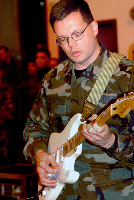 U.S. Air Force Europe band, Touch'n Go, STAFF SGT. Toby McWilliams, plays a guitar during a Commander's Call at Aviano Air Base, Italy, on Dec 8, 2004. (U.S. Force PHOTO by AIRMAN 1ST Class Desiree Hayden) (Released)