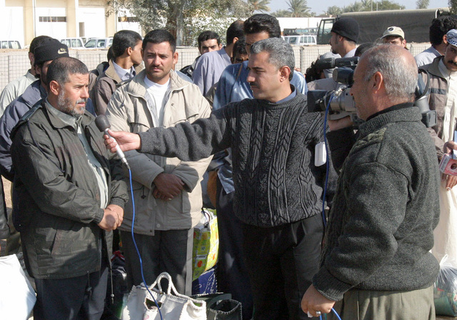 A former inmate, recently released from Abu Ghraib prison, is interviewed by a Iraqi news crew in Ar Ramadi, Iraq