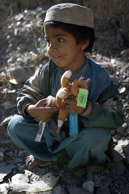 An Afghan child smiles after receiving a tooth bush, toothpaste, and a toy from Coalition Forces during Cooperative Medical Assistance in the village of Sperah, Afghanistan, in support of Operation ENDURING FREEDOM on Dec. 9, 2004.(U.S. Marine Corps official photo by CPL. Justin L. Schaeffer) (Released)