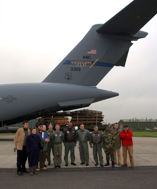 Left to right, the Sowerby family, Mississippi Air National Guard 172nd Airlift Wing LT. COL. David Buck, LT. COL. Jim Conway, LT. COL. William Hill, COL. Mike Brock, MASTER SGT. Roger Clark, SENIOR MASTER SGT. Jim Hansford, STAFF SGT. Jasmine Cook, and carpenters Mr. Tim Green and Mr. Sam McCallum pose for a photo in front of a C-17 Globemaster III cargo aircraft at Brize Norton Royal Air Force Station, United Kingdom, on Dec. 9, 2004. (U.S. Air Force PHOTO by LT. COL. David Buck) (Released)