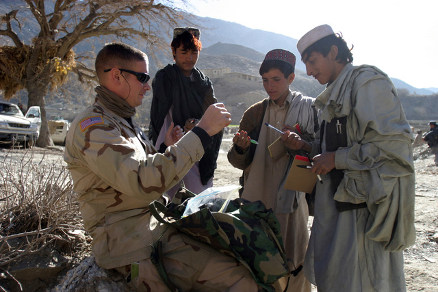 U.S. Army SGT. Brad Rhen, Journalist, Combined Joint Task Force Thunder, distributes pens and paper to Afghan children during Cooperative Medical Assistance in the village of Sperah, Afghanistan, in support of Operation ENDURING FREEDOM on Dec. 9, 2004.(U.S. Marine Corps official photo by CPL. Justin L. Schaeffer) (Released)