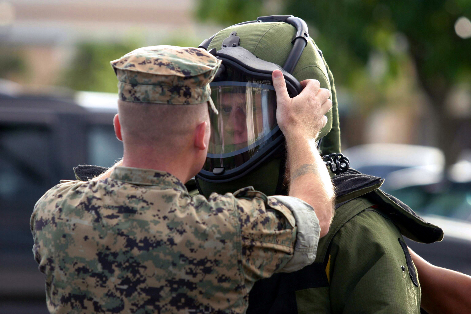 U.S. Marine Corps GUNNERY SGT. Smith helps SGT. Pretz, Explosive Ordnance Disposal SPECIALIST, Combat Service Support Group-3, attach a shield to his bomb suit while conducting training at the Marine Corps Base Hawaii, Hawaii, Post Exchange parking lot on Dec. 9, 2004.(U.S. Marine Corps official photo by CPL. Nicholas Riddle) (Released)