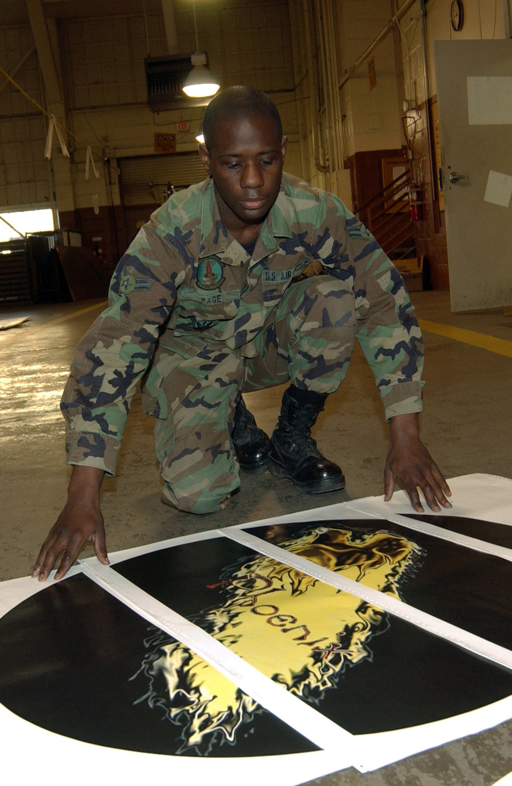 U.S. Air Force 2nd Maintenance Squadron aircraft structural maintenance journeyman AIRMAN 1ST Class Joseph Page, checks the print quality of a fresh B-52H nose art decal at Barksdale Air Force Base, La., on Dec. 10, 2004. (U.S. Air Force PHOTO by SENIOR AIRMAN Kevin A. Camara) (Released)