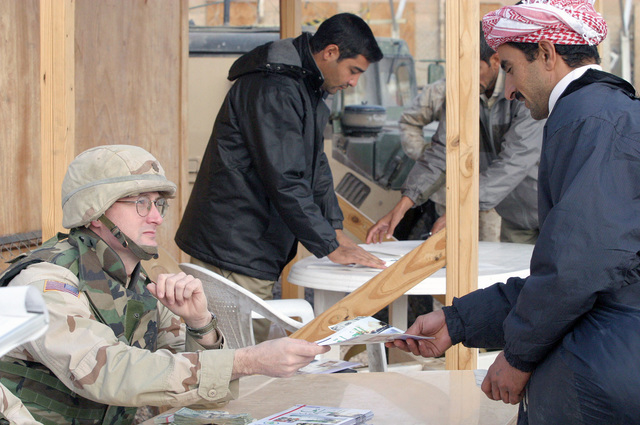 US Army (USA) Major (MAJ) Jim B. Wescott (left), HHC Company (Co), 391st Military Police (MP) Battalion (BN), hands a military information pamphlet and twenty-five US dollars to a former inmate, recently released from Abu Ghurayb prison (Abu Ghraib), as he out-processes before he boards a bus that will take him to Ar Ramadi, Iraq, to meet friends and families