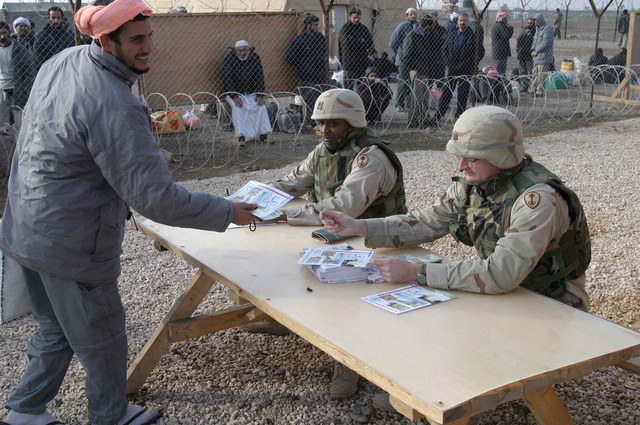 US Army (USA) Major (MAJ) Jim B. Wescott (right), HHC Company (Co), 391st Military Police (MP) Battalion (BN), hands a military information pamphlet and twenty-five US dollars to a former inmate, recently released from Abu Ghurayb prison (Abu Ghraib), as he out-processes before he boards a bus that will take him to Ar Ramadi, Iraq, to meet friends and families. USA Sergeant First Class (SFC) Curtis A. Austin, HHC Co, 391st MP BN, is seated next to MAJ Wescott