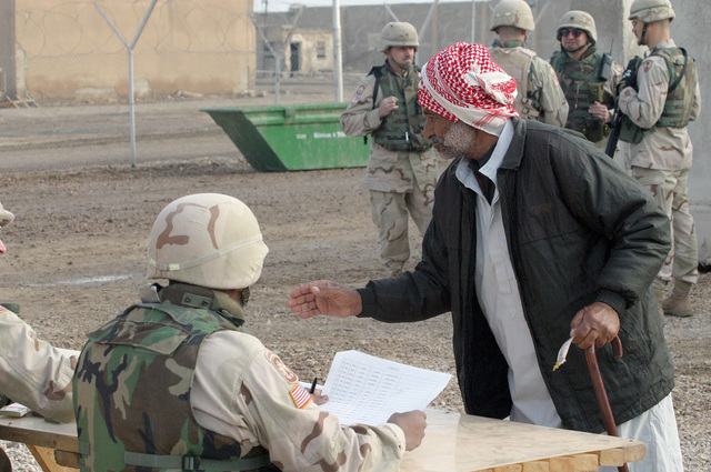 US Army (USA) Sergeant First Class (SFC) Curtis A. Austin (back to camera), HHC Company (Co), 391st Military Police (MP) Battalion (BN), checks the paperwork of former inmate, recently released from Abu Ghurayb prison (Abu Ghraib), as he out-processes before he boards a bus that will take him to Ar Ramadi, Iraq, to meet friends and families