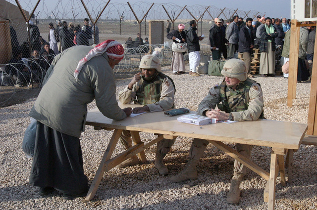 US Army (USA) Sergeant First Class (SFC) Curtis A. Austin (center), HHC Company (Co), 391st Military Police (MP) Battalion (BN), watches as a former inmate, recently released from Abu Ghurayb prison (Abu Ghraib), prepares to sign his freedom papers as he out-processes before he boards a bus that will take him to Ar Ramadi, Iraq, to meet friends and families. USA Major (MAJ) Jim B. Wescott, HHC Co, 391st MP BN, is seated next to SFC Austin