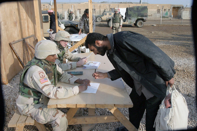US Army (USA) Sergeant First Class (SFC) Curtis A. Austin (left), HHC Company (Co), 391st Military Police (MP) Battalion (BN), watches as a former inmate, recently released from Abu Ghurayb prison (Abu Ghraib), prepares to sign his freedom papers as he out-processes before he boards a bus that will take him to Ar Ramadi, Iraq, to meet friends and families. USA Major (MAJ) Jim B. Wescott, HHC Co, 391st MP BN, is seated next to SFC Austin