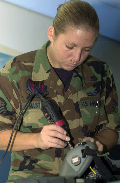 U.S. Air Force SENIOR AIRMAN Lauren Masters, a life support apprentice from the 44th Fighter Squadron, drills holes on a pressurized HGU 55/P helmet during inspection at Kadena Air Base, Japan on Dec. 13, 2004. (USAF PHOTO by SENIOR AIRMAN Tamica R. Phillips) (Released)