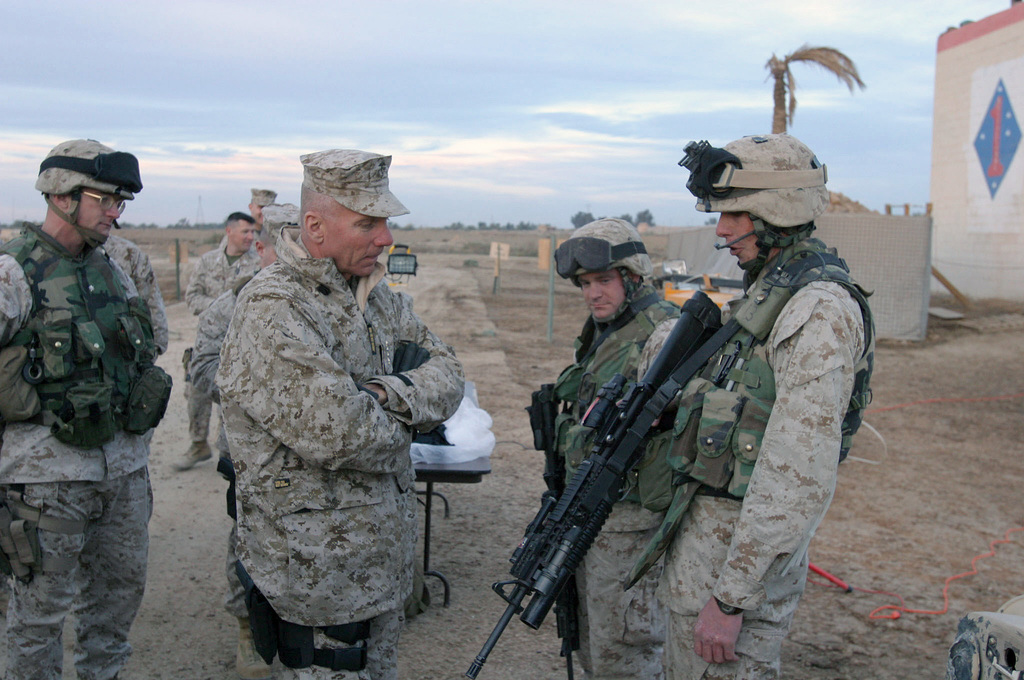 U.S. Marine Corps GEN. Michael W. Hagee (center), Commandant of the Marine Corps (CMC), listens attentively as CPL. Brad D. Widener, Fox Company, 2nd Battalion, 5th Marine Regiment, 1ST Marine Division (MARDIV) explains how well his Trijicon TA31RCO-A4 Advanced Optical Combat Gunsight (ACOG) night vision system for his 5.56 mm M16A2 rifle with 40 mm M203 grenade launcher attachment works during night patrols and raids during the CMC visit to Camp Ar Ramadi, Al Anbar Province, Iraq, Dec. 14, 2004. The 1ST MARDIV is engaged in Security and Stabilization Operations (SASO) in the Al Anbar Province in support of Operation Iraqi Freedom. (U.S. Marine Corps photo by Lance CPL. Benjamin J....