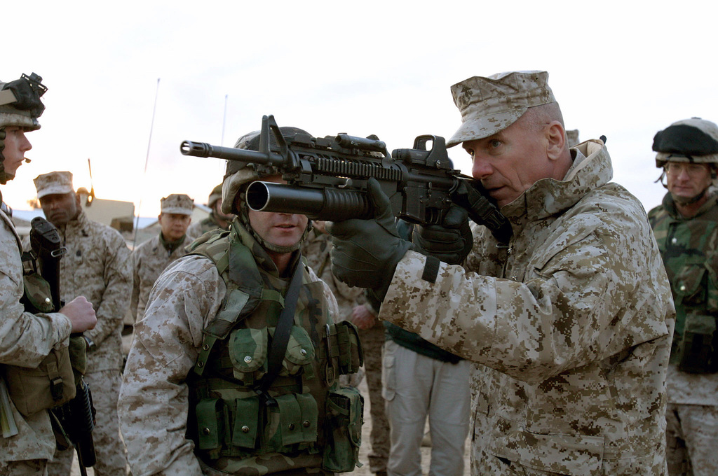 U.S. Marine Corps GEN. Michael W. Hagee (right), Commandant of the Marine Corps (CMC), looks through the EOTech 551-A65 Military Red Dot holographic weapon sight attached to the 5.56 mm M16 with 40 mm grenade launcher attachment belonging to a Marine from Fox Company, 2nd Battalion, 5th Marine Regiment, 1ST Marine Division (MARDIV) during the CMC visit to Camp Ar Ramadi, Al Anbar Province, Iraq, Dec. 14, 2004.  The 1ST MARDIV is engaged in Security and Stabilization Operations (SASO) in the Al Anbar Province in support of Operation Iraqi Freedom. (U.S. Marine Corps photo by Lance CPL. Benjamin J. Flores) (Released)