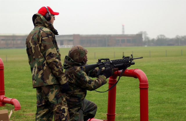 U.S. Air Force STAFF SGT. Anthony Wolf (standing), an instructor from the 48th Security Forces Squadron, assists AIRMAN 1ST Class Richard Blair during weapons qualification training on an 5.56 mm M16A2 rifle attached with an M203 grenade launcher at Royal Air Force Lakenheath, England on Dec. 15, 2004. (USAF PHOTO by AIRMAN Basic Stacey Jeanpaul) (Released)