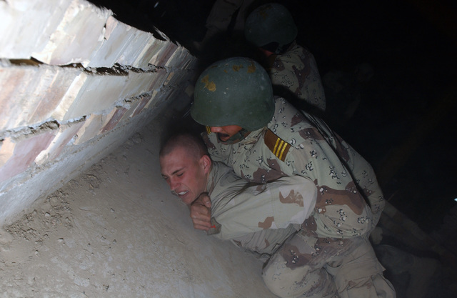 U.S. Army PFC. Ricky Hinote, of the 1ST Squadron, 4th Calvary Regiment, 1ST Infantry Division, plays the role of an unarmed combatant during training with Iraqi National Guard personnel from the 4th Company, 201st Battalion, at Forward Operating Base Wilson, near Al Dawr, Iraq on Dec. 15, 2004. (USAF PHOTO by TECH. SGT. Lee Harshman) (Released)