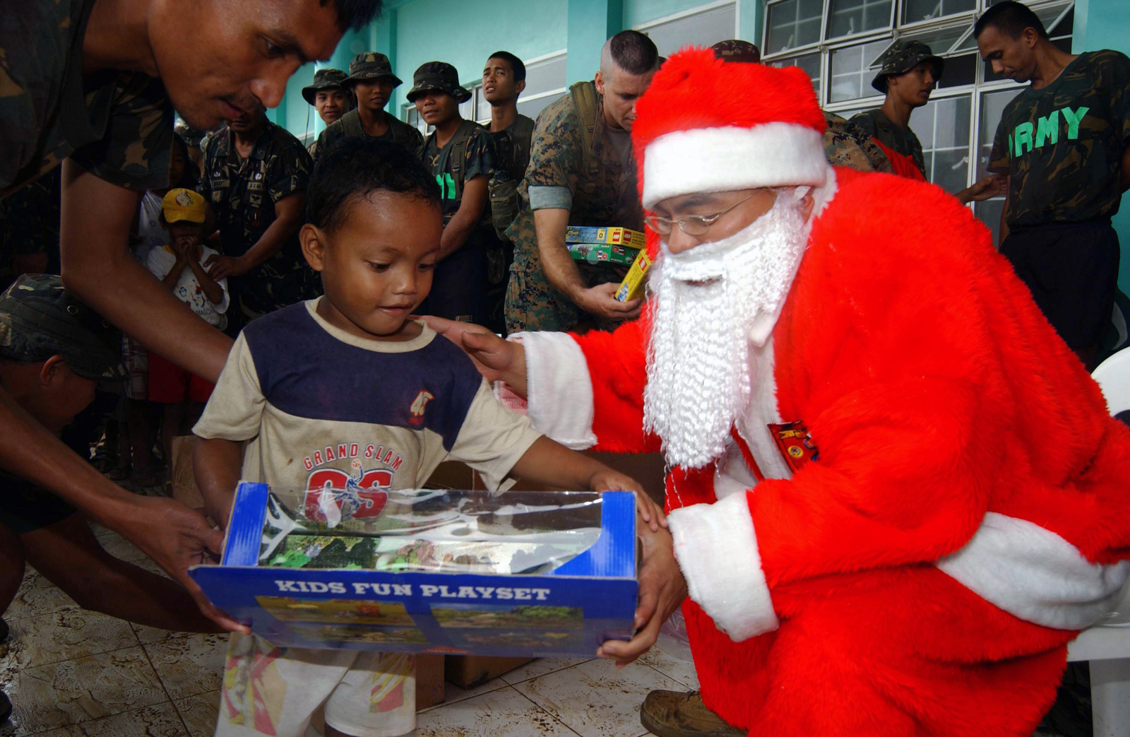 A little Filipino boy smiles as he is given a Christmas gift from a ...