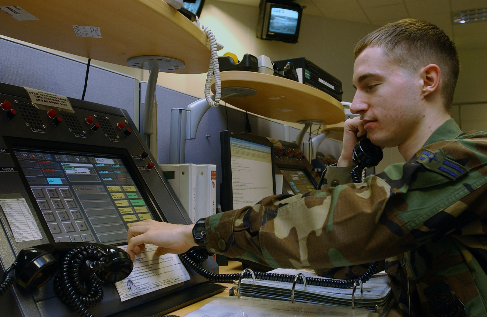 U.S. Air Force (USAF) AIRMAN 1ST Class Chad Henry, a junior emergency actions controller from the from the 352nd Special Operations Group, routes telephone and radio communications among the base leadership at the Maintenance Operations Center at Royal Air Force Mildenhall, England on Dec. 16, 2004. The command post and the maintenance operations center conduct crucial operations 24 hours a day. (USAF PHOTO by TECH. SGT. Michael D. Morford) (Released)