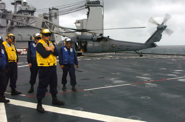 A U.S. Air Force HH-60 Pavehawk helicopter from the 33rd Rescue Squadron, Kadena Air Base, Japan, sits on the flight deck of the U.S. Navy Whidbey Island Class Dock Landing Ship USS FORT MCHENRY (LSD 43) as Sailors watch another 33rd RQS helicopter is refueled on the ship during ship deck landing qualification training during typhoon relief operations in the Philippines on Dec. 17, 2004. The helicopters landed on the ship after their last relief supply run at Quezon Province, Philippines. (USAF PHOTO by MASTER SGT Val Gempis) (Released)