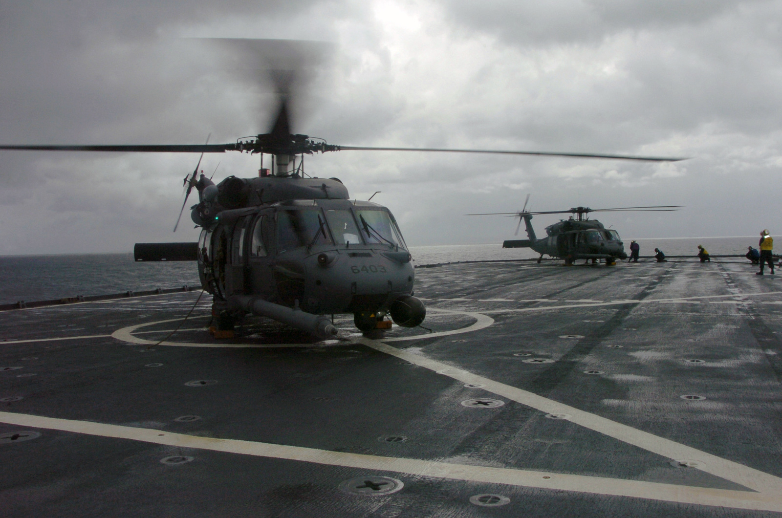 Two U.S. Air Force HH-60 Pavehawk helicopters from the 33rd Rescue Squadron, Kadena Air Base, Japan, land on the U.S. Navy Whidbey Island Class Dock Landing Ship USS FORT MCHENRY (LSD 43) during ship deck landing qualification training during typhoon relief operations in the Philippines on Dec. 17, 2004. The helicopters landed on the ship after their last relief supply run at Quezon Province, Philippines. (USAF PHOTO by MASTER SGT Val Gempis) (Released)