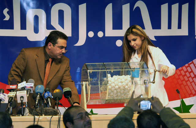 Iraqi Elections Independent Council (IECI) officials at the Baghdad Convention Center in Baghdad, Iraq, conduct a lottery selection process to determine the placement of political entities on the ballot for upcoming elections. Over 200 political party observers and 40 media gathered at the Center to witness this historical event