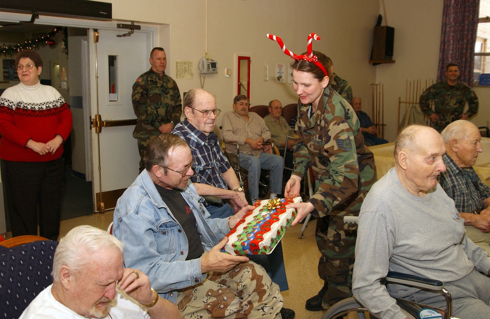 STAFF SGT. Melissa D. Rasmusson, from the 119th Maintenance Operations Flight, North Dakota Air National Guard (NDANG), based at Hector International Airport (IAP), Fargo, N.D., hands a Christmas present to a resident of the North Dakota Veterans Home in Lisbon, N.D. Dec. 21, 2004.  The residents of the nursing home look forward to recieving gifts from NDANG members each holiday season. (USAF PHOTO by SMSGT. David H. Lipp) (Released)