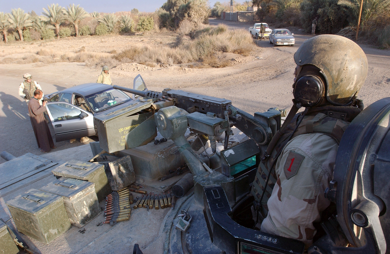 U.S. Army (USA) SPC. Adam R. Wilson (right) of Anvil Troop, 1ST Squadron, 4th Cavalry Regiment, 1ST Infantry Division, mans his .50 caliber machine gun on the turret of an M1 Abrams Main Battle Tank (MBT) while USA Soldiers check the identification of an Iraqi driver at a traffic control check point at Ad Duluiyah, Iraq on Dec. 21, 2004. (USAF PHOTO by TECH. SGT. Lee Harshman) (Released)