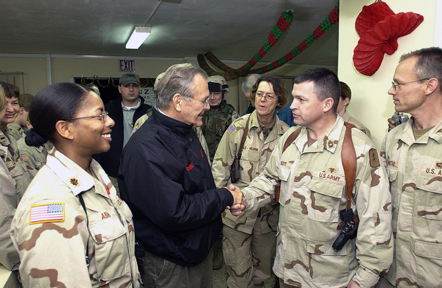 The Honorable Donald H. Rumsfeld (center), U.S. Secretary of Defense, shakes hands with U.S. Army MASTER SGT. Scott, 67th Combat Surgical Hospital, during a surprise visit by the Secretary to Mosul Airfield, Iraq, on Christmas Eve, December 24, 2004. The Secretary traveled to Iraq to show his support to service members, visiting patients and staff from the 67th Combat Surgical Hospital. (DoD photo by MASTER SGT. James M. Bowman) (Released)