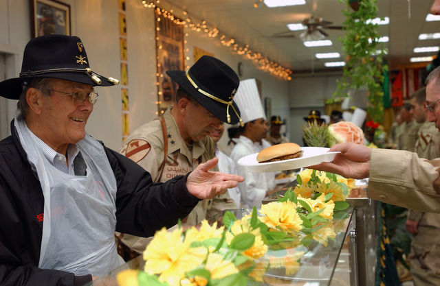 The Honorable Donald H. Rumsfeld (left), U.S. Secretary of Defense, and U.S. Army MAJ. GEN. Peter W. Chiarelli (second from left), Commanding General, 1ST Cavalry Division, both serve Christmas Eve dinner to 1ST Cavalry Division Soldiers during a surprise visit by the Secretary to the 1ST Cavalry Division Soldiers in Baghdad, Baghdad Province, Iraq, on Dec. 24, 2004. The Secretary is visiting U.S. military personnel in Mosul, Fallujah, and Baghdad on Christmas Eve during Operation Iraqi Freedom. (DoD photo by CAPT. Alan T. Amato) (Released)