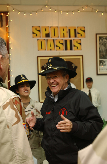 The Honorable Donald H. Rumsfeld (right), U.S. Secretary of Defense, shows off a U.S. Army 1ST Cavalry Division Hat that was just presented to him during his surprise visit to the 1ST Cavalry Division Soldiers in Baghdad, Baghdad Province, Iraq, on Dec. 24, 2004. The Secretary is visiting U.S. military personnel in Mosul, Fallujah, and Baghdad on Christmas Eve during Operation Iraqi Freedom. (DoD photo by CAPT. Alan T. Amato) (Released)