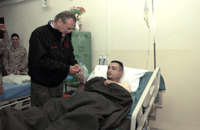 The Honorable Donald H. Rumsfeld, U.S. Secretary of Defense, presents a Purple Heart Medal to U.S. Army SGT. Chris Scott, 1ST Brigade, 25th Infantry Division, during a surprise visit to Mosul Airfield, Iraq, on Christmas Eve, December 24, 2004. SGT. Scott was wounded the day before by an improvised explosive device. The Secretary traveled to Iraq to show his support to service members, visiting patients and staff at the 67th Combat Surgical Hospital. (DoD photo by MASTER SGT. James M. Bowman) (Released)