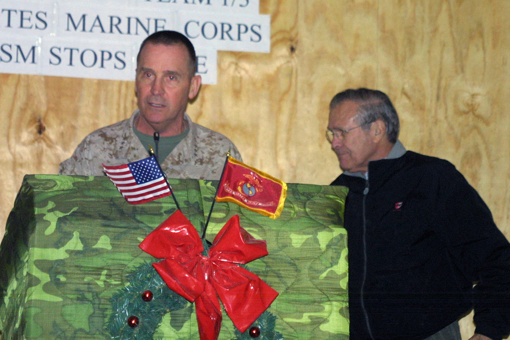 U.S. Marine Corps LT. GEN. John F. Sattler, Commanding General, 1ST Marine Expeditionary Force, prepares to introduce The Honorable Donald H. Rumsfeld, U.S. Secretary of Defense (background) to Marines, during his Christmas Eve visit at Camp Owen, Fallujah, Iraq, during Operation Al Fajr. Operation Al Fajr is an offensive operation to eradicate enemy forces within the city of Fallujah in support of continuing security and stabilization operations in the Al Anbar province, by units of the 1ST Marine Division, during Operation Iraqi Freedom II. (DoD photo by Lance CPL. Jeremy W. Ferguson) (Released)