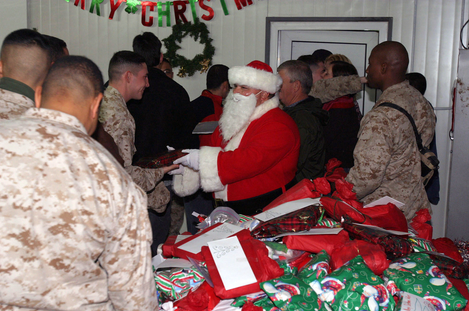 Santa Claus hands out gifts to U.S. Marines, U.S. Navy Sailors, U.S. ...