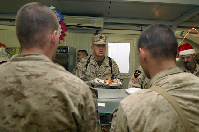 U.S. Marine Corps MAJ. GEN. Richard F. Natonski (center), Commander, 1ST Marine Division (MARDIV), serves food to Marines, U.S. Sailors and U.S. Army Soldiers on Christmas Day at Camp Ar Ramadi, Al Anbar Province, Iraq, Dec. 25, 2004.  The 1ST MARDIV is engaged in Security and Stabilization Operations (SASO) in the Al Anbar Province in support of Operation Iraqi Freedom. (U.S. Marine Corps photo by Lance CPL. Benjamin J. Flores) (Released)