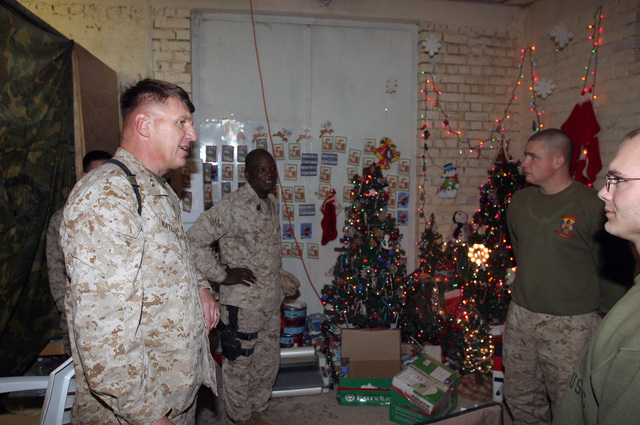 U.S. Marine Corps MAJ. GEN. Richard F. Natonski (left), Commander, 1ST Marine Division (MARDIV) and SGT. MAJ. Wayne R. Bell (rear), visit the Marines of Communications Company on Hurricane Point in the city of Ar Ramadi, Al Anbar Province, Iraq, on Christmas Day, Dec. 25, 2004. GEN. Natonski and SGT. MAJ. Bell made their rounds to all of the camps in the area wishing the Marines, U.S. Navy Sailors and U.S. Army Soldiers a Merry Christmas.  The 1ST MARDIV is engaged in Security and Stabilization Operations (SASO) in the Al Anbar Province in support of Operation Iraqi Freedom. (U.S. Marine Corps photo by Lance CPL. Benjamin J. Flores) (Released)