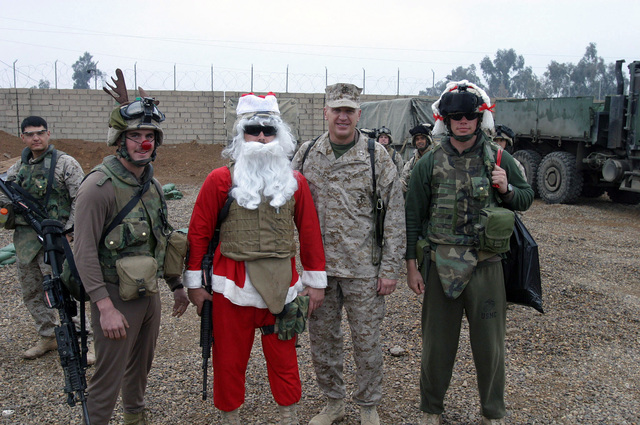 U.S. Marine Corps MAJ. GEN. Richard F. Natonski (second from right), Commander, 1ST Marine Division (MARDIV) poses for a group photo with Santa Claus, Mrs. Claus and Rudolph the red-nosed reindeer on Snake Pit, Ar Ramadi, Al Anbar Province, Iraq. The 1ST MARDIV is engaged in Security and Stabilization Operations (SASO) in the Al Anbar Province in support of Operation Iraqi Freedom. (U.S. Marine Corps photo by Lance CPL. Benjamin J. Flores) (Released)
