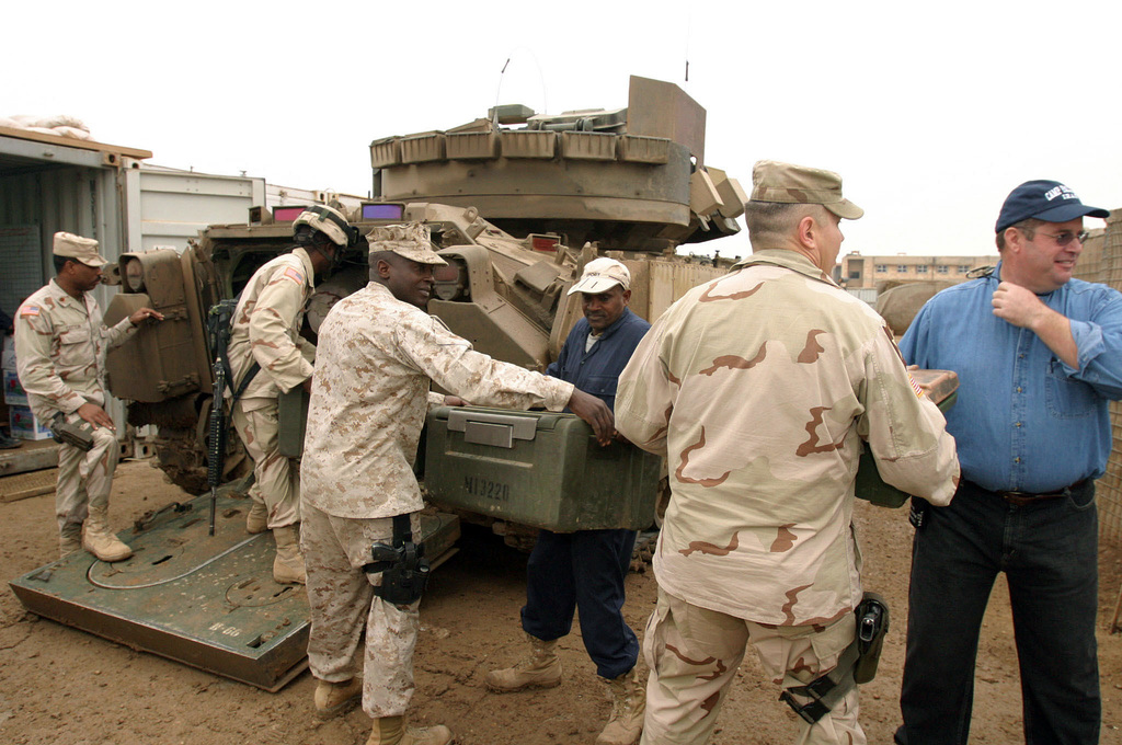 U.S. Marine Corps SGT. MAJ. Wayne R. Bell (center), Sergeant Major, 1ST Marine Division (MARDIV), joins in to help load Christmas Dinner on an AAV7A1 Amphibious Assault Vehicle, also knows as an AmTrac by the Marines, that is delivering food to Marines, U.S. Sailors and U.S. Army Soldiers on Combat Out Post in Ar Ramadi, Al Anbar Province, Iraq, Dec. 25, 2004.  The 1ST MARDIV is engaged in Security and Stabilization Operations (SASO) in the Al Anbar Province in support of Operation Iraqi Freedom. (U.S. Marine Corps photo by Lance CPL. Benjamin J. Flores) (Released)
