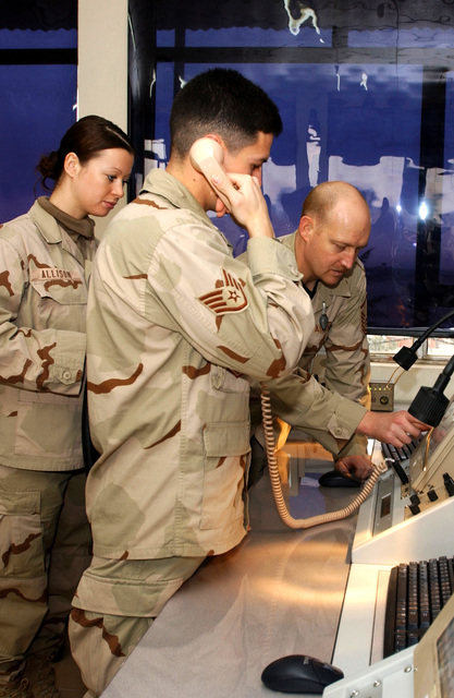 U.S. Air Force MASTER SGT. Daniel Olson (right), SENIOR AIRMAN Natasha Allison (left) and STAFF SGT Lenn Bassett (foreground), all air traffic controllers from the 506th Expeditionary Operations Support Squadron, perform an operational check on an equipment at the control tower at Kirkuk Air Base, Iraq on Dec. 26, 2004. (USADF PHOTO by STAFF SGT. Adrian Cadiz) (Released)