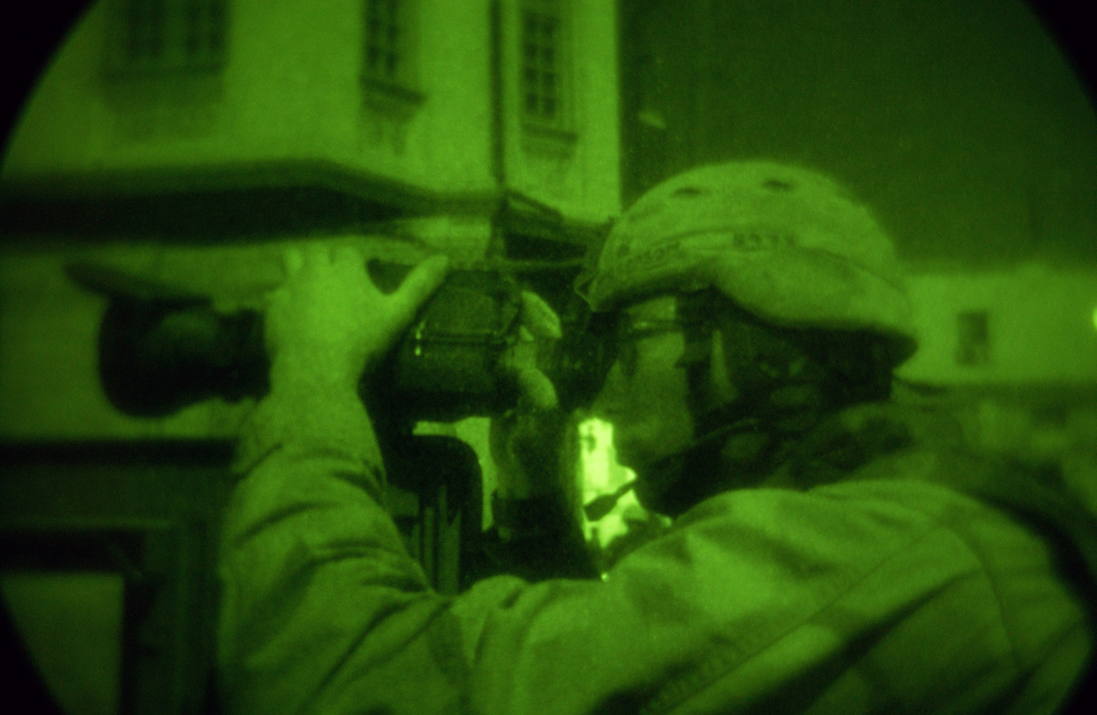 A US Army (USA) Soldier assigned to the 2nd Brigade Combat Team (BCT), 162nd Infantry Battalion, uses his infrared camera to search down alleys near a mosque during a nighttime raid in Al-Tharwa, Iraq, during Operation IRAQI FREEDOM. (SUBSTANDARD)