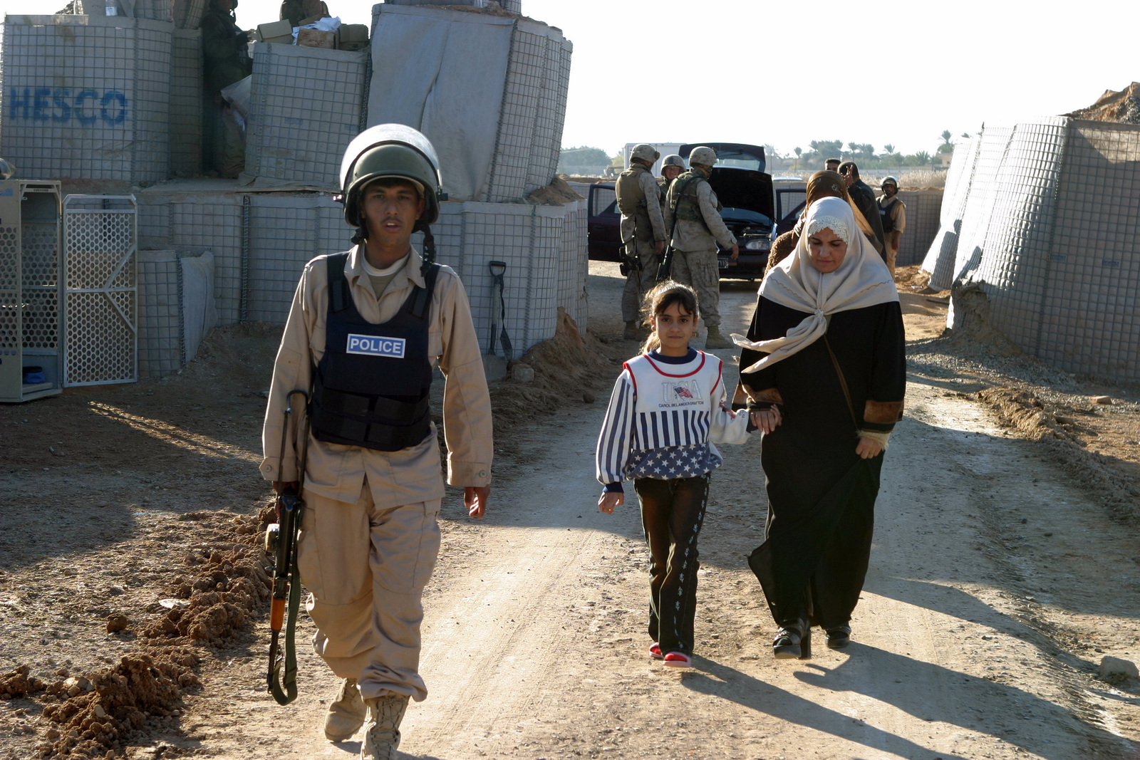 An Iraqi Police (IP) Policeman escorts an Iraqi woman and her daughter to  the female search ...