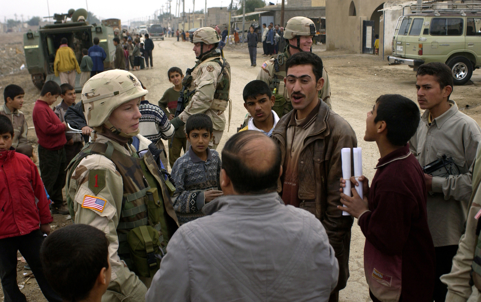 U.S. Army STAFF SGT. Kelly Tiffany (left) from the 570th Physcological Operations attached to the 1ST Battalion, 278th Regimental Combat Team, 1ST Infantry Division, talks to Iraqis on a street during a patrol at Balad Ruz, Iraq, on Dec. 30, 2004. (USAF PHOTO by STAFF SGT. Shane A. Cuomo) (Released)