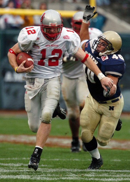 US Naval Academy (USNA) Midshipman (MIDN) Line Backer David Mahoney (40) attempts to tackle New Mexico (NM) Quarterback Kole McKamey (12) in the First quarter of play against the Lobos of NM at the Emerald Bowl in San Francisco. At halftime Navy led the Lobos 24-19