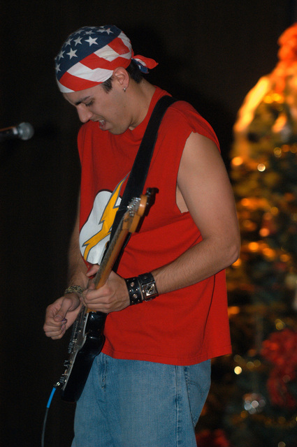 """Sam Wright of the rock band,""""Off the Wall,""""plays his guitar for Marines, Sailors, Soldiers, and Civilian Contractors of Al Asad, Iraq, at the base theater on New Year's Eve. Dec. 31, 2004. (U.S. Marine Corps photo by Lance CPL. William Dubose) (Released)"""