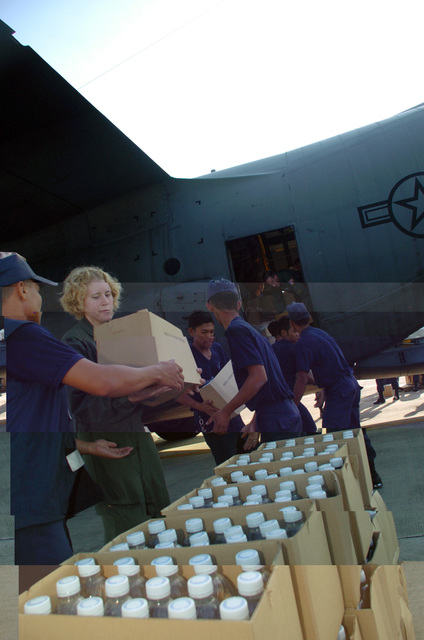 U.S. Air Force 1ST LT. Andrea R. Seefeldt, a C-130 Hercules cargo aircraft navigator from the 36th Airlift Squadron, Yokota Air Base, Japan, together with Thailand military personnel load boxes of bottled water inside her C-130 aircraft during tsunami relief operations at Phuket, Thailand, on Dec. 31, 2004. The relief supplies are bound for Southeast Asia as part of a disaster relief operation following a 9.0 magnitude earthquake that struck off the coast of Indonesia causing a tsunami that have affected 12 countries and has killed at least 100,000 people. (USAF photo by SSgt Cohen A. Young) (Released) (SUBSTANDARD)