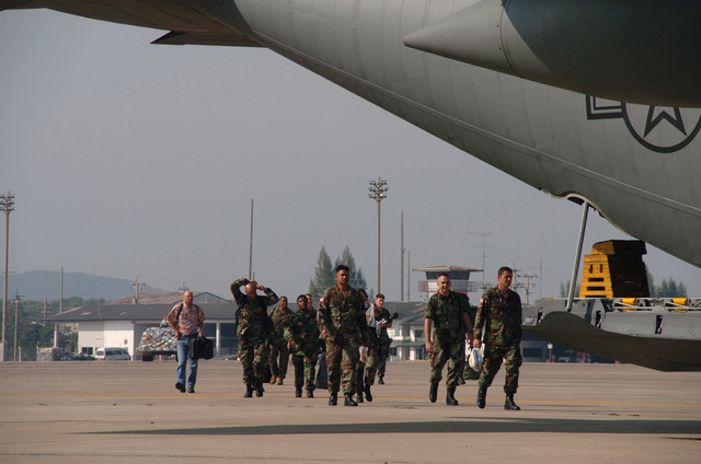 U.S. military personnel from the Joint POW/ MIA Command (JPAC) Mortuary Affairs team prepare to board a U.S. Air Force C-130 Hercules cargo aircraft during Operation Unified Assistance at Utapao Air Base, Thailand, on Jan. 3, 2005. The team is heading for Bangkok, Thailand. More than 18,000 U.S. military personnel are providing humanitarian assistance in Southwest Asia after a 9.0 magnitude earthquake on Dec. 26, 2004, triggered devastating tsunamis that killed over 250,000 people in the region. (USAF PHOTO by TECH. SGT. Cohen A. Young) (Released)