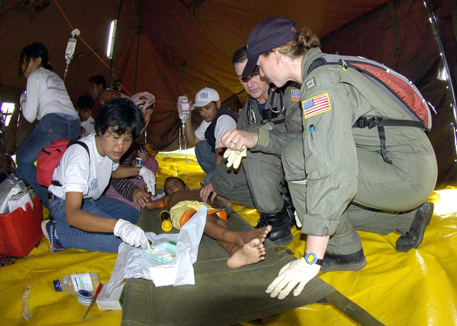 US Navy (USN) Lieutenant (LT) Lisa Peterson (front right) and USN LT Mark Banks, tend to a patient flown-in by a USN helicopter to a temporary triage site in Aceh, Sumatra. Medical teams from USS ABRAHAM LINCOLN (CVN 72) [not shown], Carrier Air Wing 2 (CVW-2) and the International Organization for Migration (IOM) set-up a triage site on Sultan Iskandar Muda Air Force Base (AFB), in Banda Aceh, Sumatra, to provide initial medical care to victims of the Tsunami-stricken area