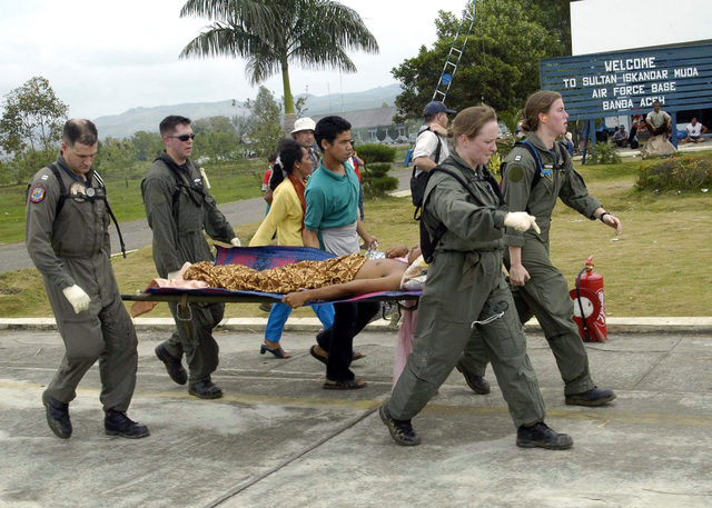 US Navy (USN) Lieutenant (LT) Mark Banks (left), USN CHIEF Hospital Corpsman (HMC) Jim Jones, USN Hospital Corpsman First Class (HM1) Rebecca McClung, and USN LT Lisa Peterson (right), use a stretcher to carry a patient, flown-in by a USN helicopter, to a temporary triage site on Sultan Iskandar Muda Air Force Base (AFB) Banda Aceh, Sumatra. Medical teams from USS ABRAHAM LINCOLN (CVN 72) [not shown], Carrier Air Wing 2 (CVW-2) and the International Organization for Migration (IOM) set-up the triage site on the base to provide initial medical care to victims of the Tsunami-stricken area